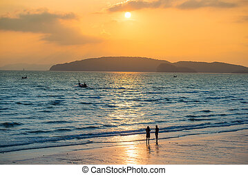 Silhouettes of people on beach at sunset