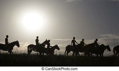Silhouettes of people on horses against sunrise