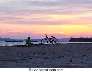 Silhouettes of people on the beach at sunset