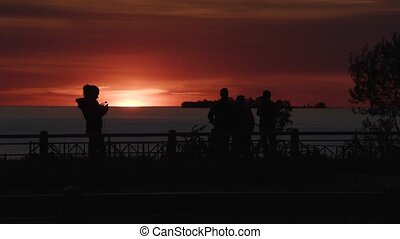 silhouettes of people on the city promenade during sunset.