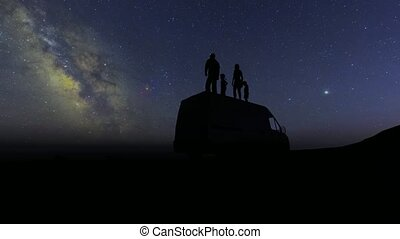 Silhouettes of people stand on the roof of the car and look at the stars. Family mother daughter son father. Happy family. 4k