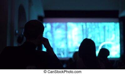 Silhouettes of people watching movie in dark cinema hall