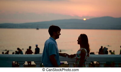 Silhouettes of romantic couple on sunset. Sea background. man and woman kiss