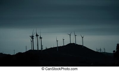 Silhouettes of rotating wind generators against blue evening...