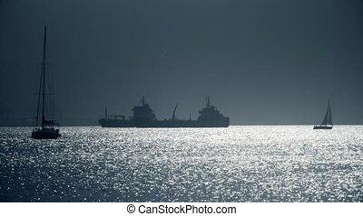 Silhouettes of sailboats and cargo ship near Gibraltar -...