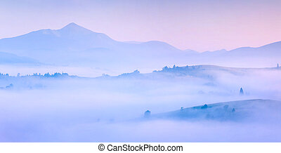 Silhouettes of the mountains in the morning mist. Summer, sunrise