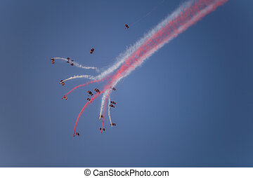 Silhouettes of the skydiver team flying in formation and...