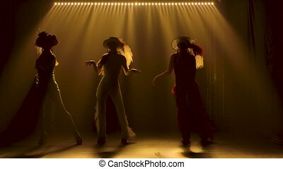 Silhouettes of three slender women in tight-fitting suits dancing incendiaryly. Shot in a dark studio with smoke and yellow light. Slow motion