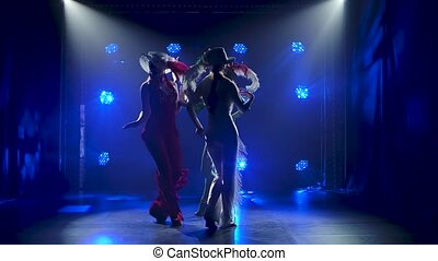 Silhouettes of three young women in tight-fitting overalls and hats dancing against the backdrop of blue spotlights. Theatrical female dance show. Slow motion