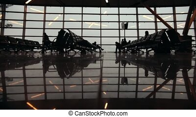 Silhouettes of travelers in Airport International Terminal. People walking around. Feet close up