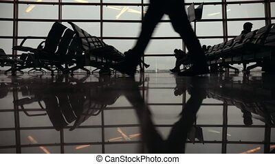 Silhouettes of travelers in Airport International Terminal. People walking around. Feet