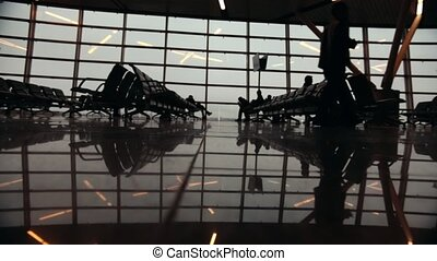 Silhouettes of travelers in Airport International Terminal. People walking around.