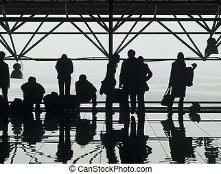 Silhouettes and reflections of passenger waiting at an airport