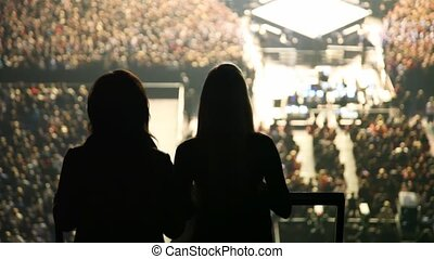 silhouettes of two dancing women against concert hall