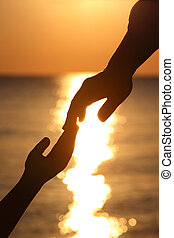 Silhouettes of two hands child and mother adjoin fingers in evening at seaside during sunset