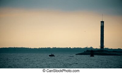 Silhouettes of two men in a boat near lighthouse at dusk