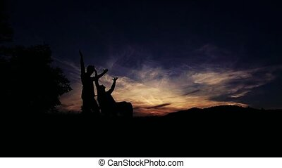 Silhouettes of two men, one in wheelchair, outdoors in...