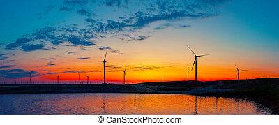 Silhouettes of wind generators power plant on lake at sunrise