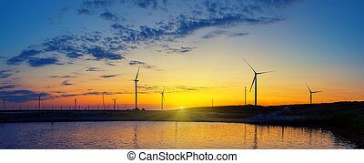 Silhouettes of wind generators power plant on lake at sunset