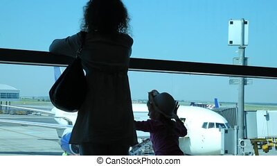 Silhouettes of woman with daughter look through window at planes at airport