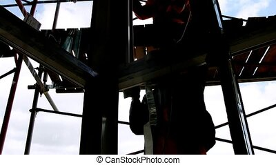 Silhouettes of workers are visible behind glass on scaffold,...