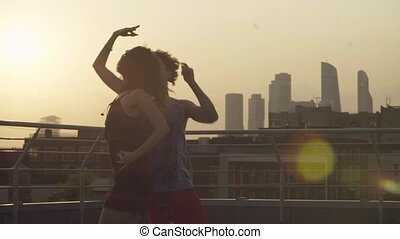Silhouettes of young couple dancing on sunset