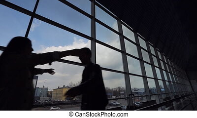 Silhouettes of young couple meeting in airport.