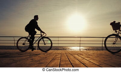 Silhouettes of young couple riding bicycles on sea...