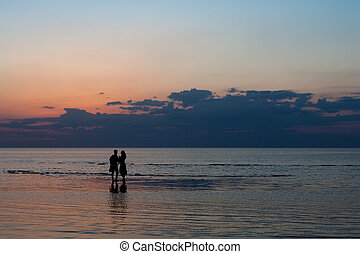 Silhouettes of young people on the beach at sunset