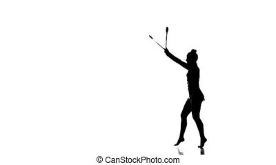 Silhouettes Tender gymnast  dance with juggling clubs, slow motion
