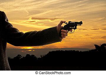 silhoutte of a man with a handgun at sunset