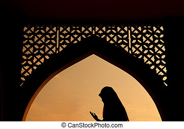 silhoutte of muslim woman praying during fasting holy month...