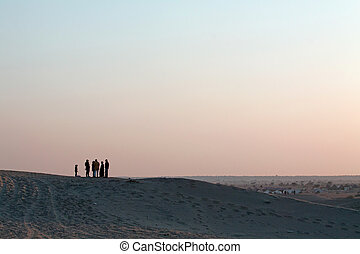 Silhoutted People Group and Child on Sand-dunes at Dusk