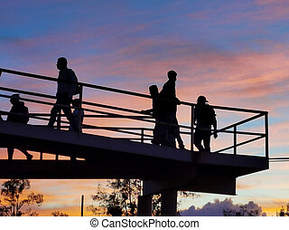 Silhouttes of people crossing a bridge with a beautiful orange sunset
