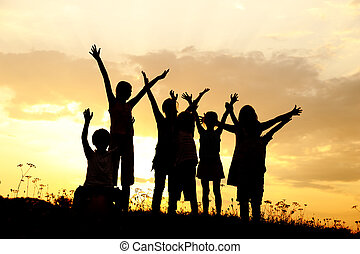silhuet, gruppe, i, glade, børn spille, på, eng, solnedgang,...