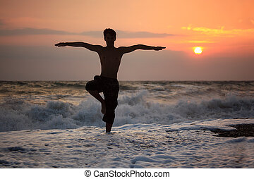 silhuet, guy, yoga, på, solnedgang, bølgede, strand