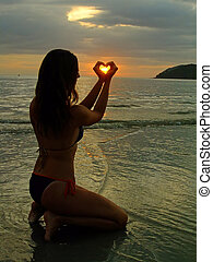 silhuet, i, ung kvinde, indgåelse, hjerte form, hos, hende, hænder, hos, solnedgang