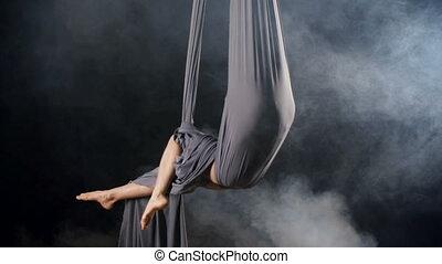 Silk Hammock - Yoga practitioner sitting in hammock formed...