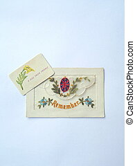 World War 1 silk embroidered postcard with the word 'Remember' and British flag with flowers embroidered. Small insert card printed with 'A Kiss from France and yellow flowers and green leaves.