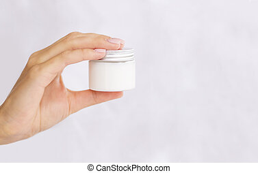 Silky skin female hand holds glass jar with white organic skin cream. Copy space for logo on a bottle. Beauty banner concept