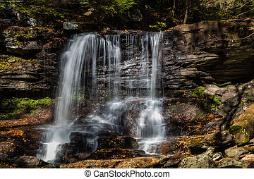 Waterfalls are surrounded by colorful fall foliage at Ricketts Glen State Park in Benton, PA