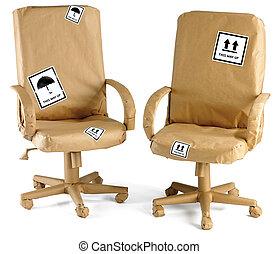 sillas de la oficina, enrolló, en, papel marrón, listo, para, un, movimiento, aislado, en, un, fondo blanco