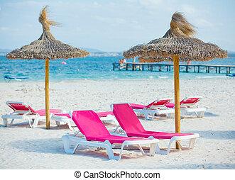 sillas, y, paraguas, en la playa