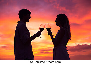 Sillhouette of couple drinking wine at sunset