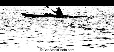 Sillouette of man kayaking on lake in the morning