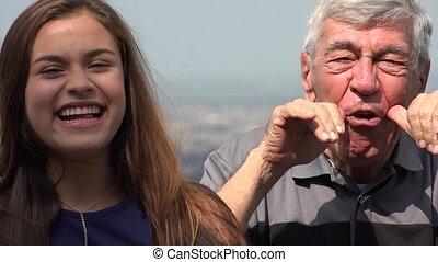 Silly Hispanic Grandfather And Granddaughter Having Fun