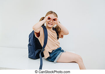 Silly little girl having fun, grimacing, making googles gesture. Over white