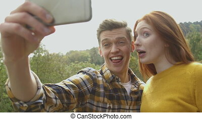 Silly Smart Phone Selfies - Young couple taking silly...