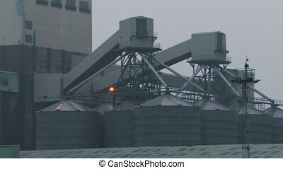 Silos and a smoking building - A right to left panning shot ...