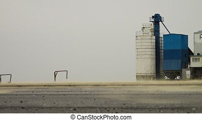 Silos and Machinery - Steady, low angle, medium wide shot of...